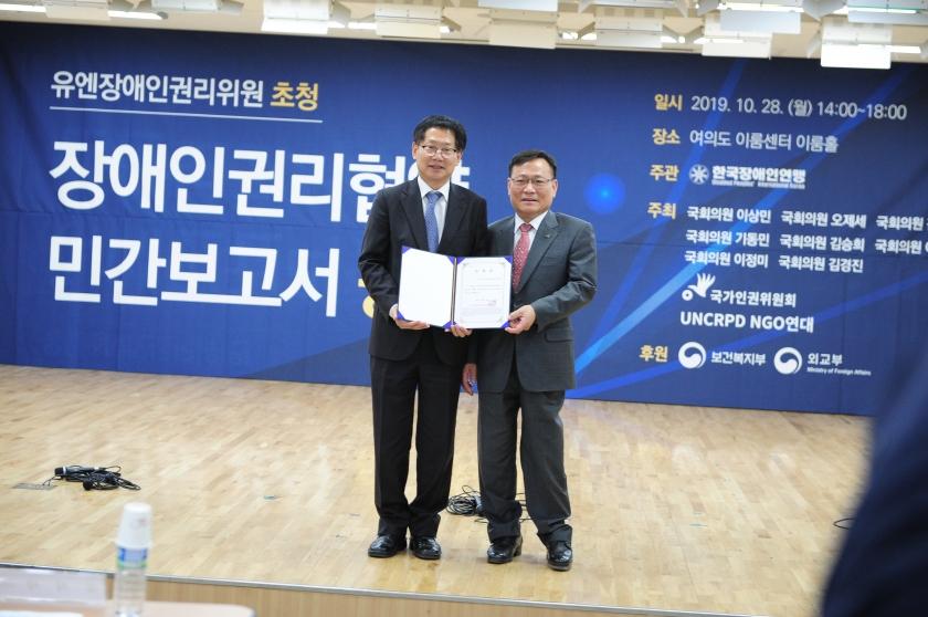 오제세 의원과 김광환 대표가 함께 위촉장을 들고있는 모습을 정면에서 찍은 사진