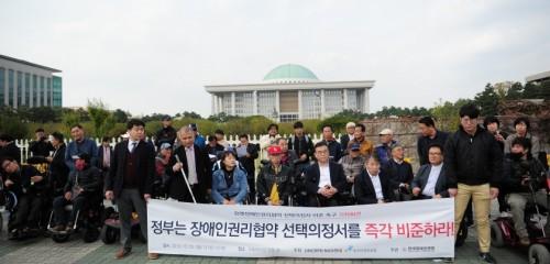 정부는 장애인권리협약 선택의정서를 즉각 비준하라 현수막을 들고 있는 단체 모습을 정면으로 찍은 사진01